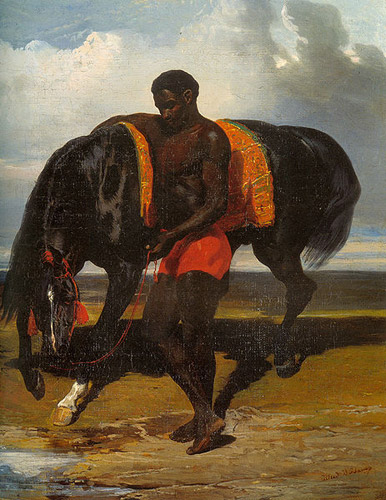 African American holding a horse at the edge of a sea