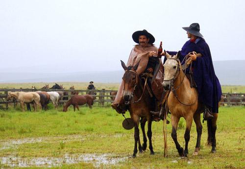 Two men on horseback sharing a beer