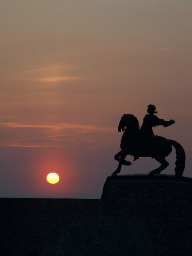 Man and horse statue at sunset